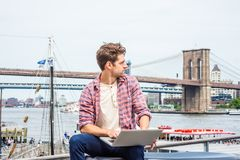 Young American Man traveling, working in New York. Wearing red patterned shirt, white undershirt, sitting by river, working on laptop computer, looking away Royalty Free Stock Images