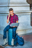 Young American Man working on laptop computer, talking on cell p Stock Photos