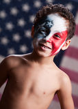 Young American Patriot. Adorable, mixed race boy wearing red, white and blue face paint.  Blurred American flag in the background Stock Images