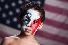 Young American Patriot. Adorable, mixed race boy wearing red, white and blue face paint.  Blurred American flag in the background Stock Photos