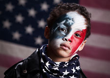 Young American Patriot. Adorable, mixed race boy wearing red, white and blue face paint.  Blurred American flag in the background Royalty Free Stock Photography