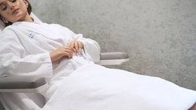 Young american woman is lying on table and getting nail therapy treatment. Female doctor is sitting and holding lady foot by hand in gloves for retreat stock video