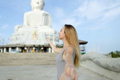 Young american woman making photo by selfie stick near white statue of Buddha in Phuket. stock images