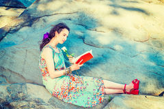 Young American Woman reading book, sitting on rocks, relaxing at Stock Image