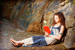 Young American Woman reading red book, sitting on ground, travel Royalty Free Stock Images