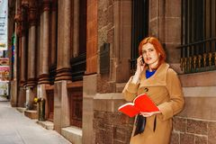 Young American Woman reading red book, talking on cell phone out. American Woman with red hair reading red book, talking on cell phone outside in New York Royalty Free Stock Image