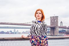Young American Woman traveling in New York,. Young American Woman with red hair traveling in New York, wrapping around body with patterned scarf in cold weather royalty free stock image