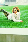 Young American Woman relaxing on green lawn Stock Image
