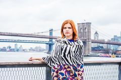 Young American Woman traveling in New York. Wrapping around body with patterned scarf in cold weather, frowned, thinking. Manhattan, Brooklyn bridges on stock images