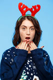 Young amused beautiful brunette girl in knited sweater and christmas reindeer antlers smiling  over blue background. Royalty Free Stock Image