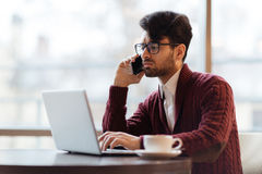 Young analyst. Attractive businessman looking at lapto pdisplay while talking on the phone in cafe royalty free stock photo