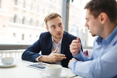 Brokers talking. Young analysts consulting at start-up meeting in cafe Royalty Free Stock Photo