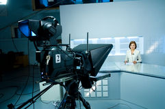 Young anchorwoman at TV studio. Young television announcer at studio during live broadcasting Stock Photos