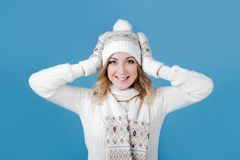 Free Young And Attractive Woman In A Knitted Sweater. Pulls Cap, Blue Background Royalty Free Stock Photo - 103113325