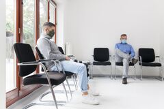 Free Young And Mature Man With Face Masks Sitting In A Waiting Room Of A Hospital Or Office Royalty Free Stock Photo - 198107745