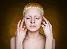 Young androgynous girl. With white hair in the studio on yellow  textured background Royalty Free Stock Photos