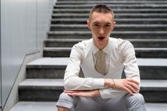 Young androgynous homosexual LGTB businessman sitting on stairs stock image
