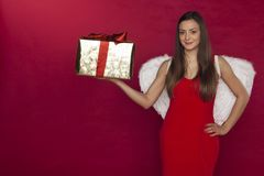Young angel woman, beautiful white wings and a wonderful gift. Red background Royalty Free Stock Photo