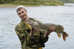 Young angler holds and looks at the big pike Royalty Free Stock Image