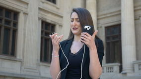 Young angry and anxious woman crying while her phone turns off due to discharged low battery in the city. Young angry and anxious woman crying while her phone stock video footage