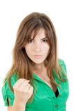 Young angry brunette woman throwing punch with fist to camera stock photography