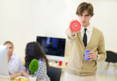 Young angry businessman pointing his watch as concept of arrive late at the work. At modern startup office Stock Photos