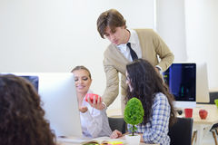 Young angry businessman pointing his watch as concept of arrive late at the work. At modern startup office Stock Photo