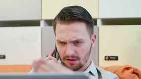 A Young Angry Man Talking on the Mobile Indoors stock photography