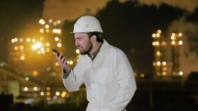 Young angry engineer in helmet and white robe shouting on phone standing by gas refinery.