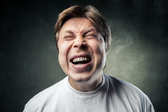 Young angry man over dark grey background Royalty Free Stock Photo