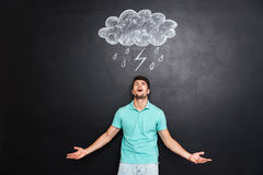 Young angry man shouting over blackboard with drawn raincloud Stock Images