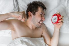 Young angry man is waking up and wants to damage his alarm clock with fist Royalty Free Stock Photo