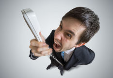 Young angry manager is calling and shouting to the telephone. View from above Royalty Free Stock Images