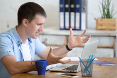 Young angry office man looking at laptop computer. Young stressed businessman sitting with laptop gesticulating with angry and furious expression. Annoyed Royalty Free Stock Images