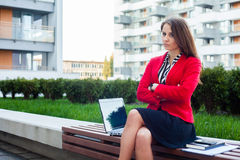 Young angry professional business woman sitting outdoor with arm. S crossed. In the background office block Royalty Free Stock Image