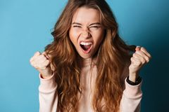 Young angry screaming woman standing isolated. Image of young angry screaming woman standing isolated over blue wall background. Looking camera Royalty Free Stock Photography