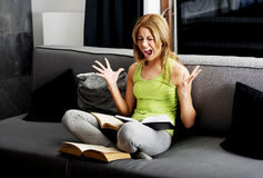 Young angry woman learning to exam on a sofa. Royalty Free Stock Photos