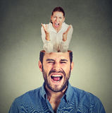 Young angry woman screaming inside head of a frustrated guy. Portrait of a young angry women screaming inside head of a frustrated guy on gray background royalty free stock photography