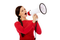 Young angry woman screaming through a megaphone Stock Photos