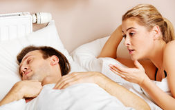Young angry woman talking to her sleeping husband Royalty Free Stock Photos