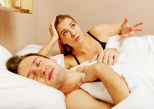 Young angry woman talking to her sleeping husband Stock Images