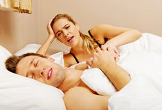 Young angry woman talking to her sleeping husband Stock Photos