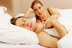 Young angry woman talking to her sleeping husband Royalty Free Stock Images