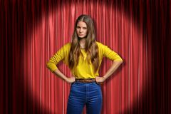Young angry woman wearing jeans and yellow shirt on red stage curtains background stock photography