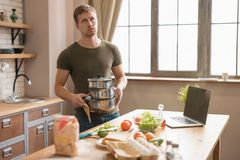 Young annoyed man with casseroles in his hands standing in well-equipped kitchen looking tired and desperate , sunday morning