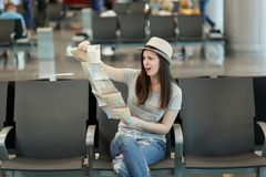 Young annoyed traveler tourist woman holding paper map, search route, wait in lobby hall at international airport. Passenger traveling abroad on weekends royalty free stock photo