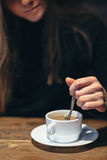 Young anonymous woman stirring coffee in a cup Stock Photography