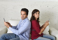 Young antisocial mobie phonel addict couple ignoring each other using internet compulsively. Young attractive antisocial couple of men and women together at home stock images