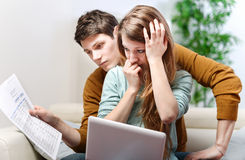 Young anxious couple consults their bank account Royalty Free Stock Photography