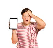 Young anxious holding his head with hands. Worried guy holding tablet blank screen. emotional guy on white background royalty free stock image